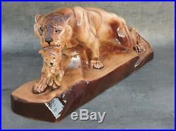 Groupe art-déco faïence représentant une lionne portant son lionceau signé J J